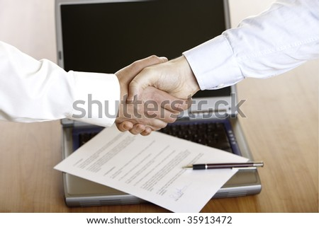 Business handshake after the signing of a contract with laptop and contract in background.