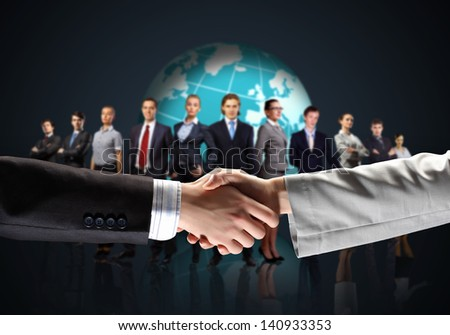 business handshake against black background and standing businesspeople