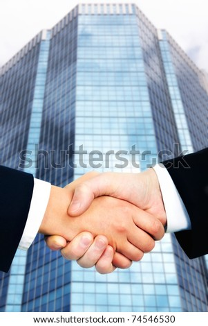 Business handshake against office building