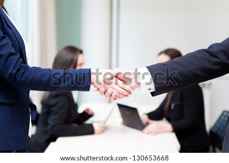 Business handshake at the office with bussiness people on background