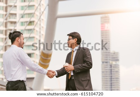 Business handshake. Handshake of two business men closing a deal city blackground #615104720