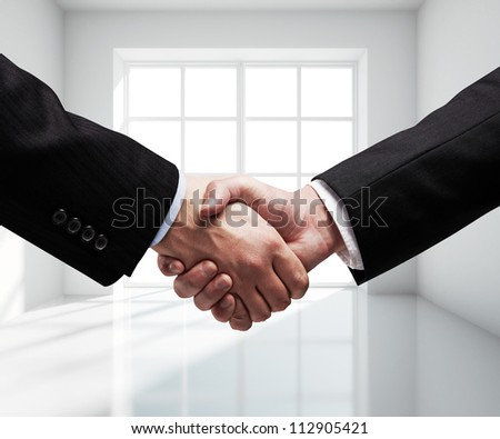 business handshake in gray room