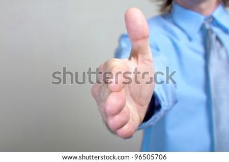 Business handshake, let's make a deal. Businessman in blue shirt offering a handshake.