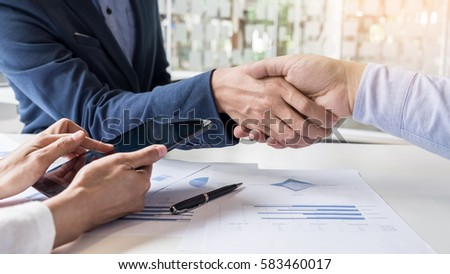 Business handshake of two men demonstrating their agreement to sign agreement or contract between their firms, companies, enterprises #583460017