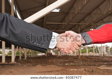 Business handshake on construction site of shopping center