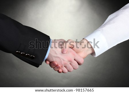 Business handshake on gray background