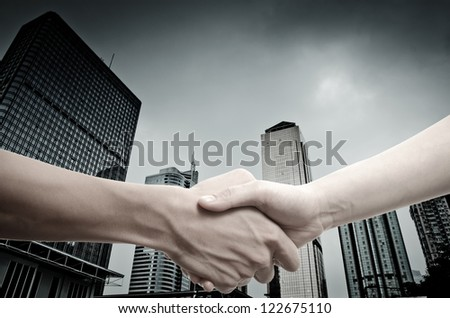 business handshake on modern city