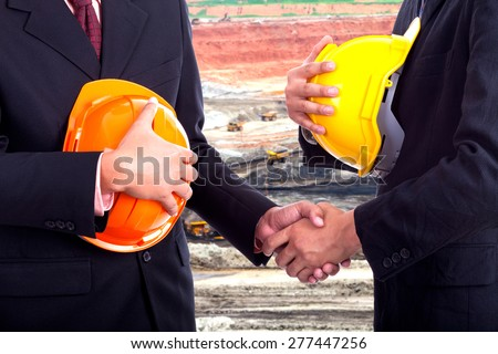 Business handshake on the background mines.