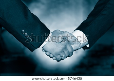 Business handshake over abstract blue background