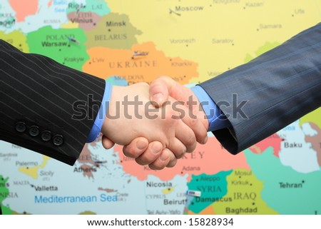 Business handshake over world map background
