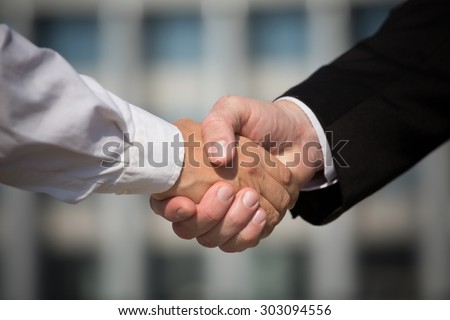 Business handshake, the deal is finalized between two enterprises. Man in black suit and woman in white one have signed the agreement.