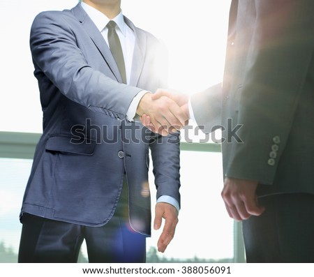 Business handshake. Two businessman shaking hands in the office. #388056091