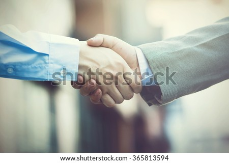 Business handshake. Two businessman shaking hands (Vintage tone)