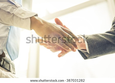 Business handshake. Two businessmen reaching an agreement and making a deal.
