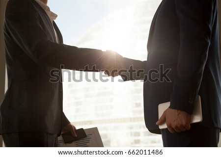 Business handshake, two businessmen wearing suits handshaking after negotiations, male partners shake hands, big city building at background, hiring accounting firm, support, help. Close up side view