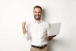 Business. Happy manager winning online, rejoicing with fist pump, holding laptop and triumphing, standing over white background