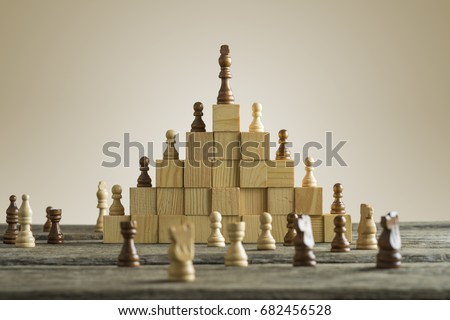 Business hierarchy; ranking and strategy concept with chess pieces standing on a pyramid of wooden building blocks with the king at the top with copy space.