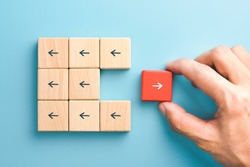 Business icon for innovative, solution, Unique, think different and individual concept, Businessman hand choose red wooden blocks with arrow individual pointing in the different way