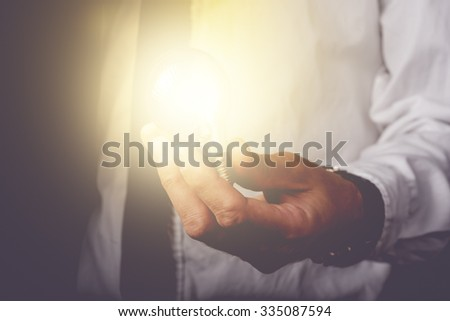 Business idea and vision, businessman holding light bulb, concept of new ideas, innovation, invention and creativity, retro toned image, selective focus.