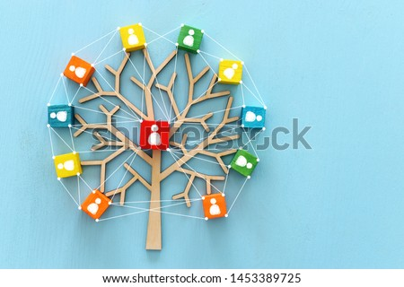 Business image of wooden tree with people icons over blue table, human resources and management concept