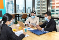 Business in new normal. Office workers wearing face mask and protection while having internal meeting for new business strategy or plan. Technology for social distancing and new normal