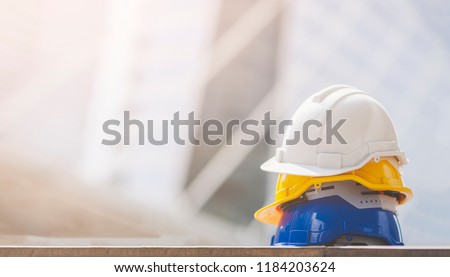 Business Industrial Safety Health Employee Concept . white, yellow and blue hard safety helmet hat for safety project of workmen as engineer or worker, on concrete floor on construction site or city