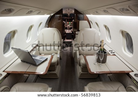 Business Interior Jet Airplane with computer laptop and Champagne on the tables.