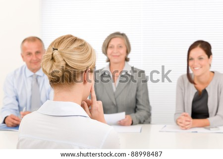 Business interview young woman being examined by professional manager team - stock photo