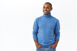 Business, investmenent and profit concept. Portrait of pleased, happy young elegant african-american male entrepreneur in blue turtleneck, hold hands in pockets, looking left with satisfied smile
