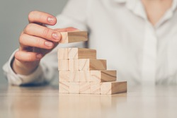 Business investment concept - hand builds a ladder from wooden blocks. Close up.