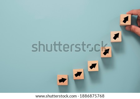 Business investment growth concept , Businessman holding wooden cube block which print screen up and increase black arrow on blue background. Stock foto ©