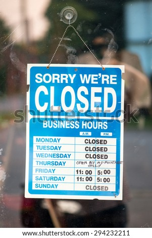 Business is slow. A sign on a store\'s glass door shows that the store is closed for most of the week. Slow down.