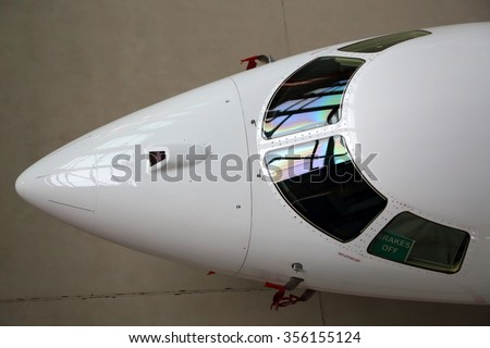 Business jet airplane cockpit glass and nose fairing.