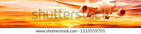 business jet airplane with gear down fly on dramatic sunset sky background corporate air travel commercial airline modern passenger plane aerial front view landscape ultra wide banner panorama photo