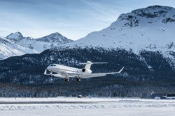 Business jet Landing at an airfield in the mountains of Switzerland. The way wealthy people travel. A beautiful mountain scenery in the background.