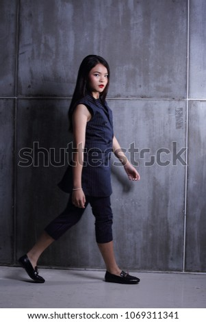 Business Kid Girl in formal suit stand on dark abstract background, studio lighting copy space for text logo, black hair eleven years old full length snap body, walk toward to future #1069311341