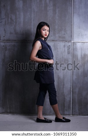Business Kid Girl in formal suit stand on dark abstract background, studio lighting copy space for text logo, black hair eleven years old full length snap body #1069311350