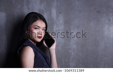 Business Kid Girl in formal suit stand on dark abstract background, studio lighting copy space for text logo, black hair eleven years old portrait half body, talking smartphone manage iot #1069311389