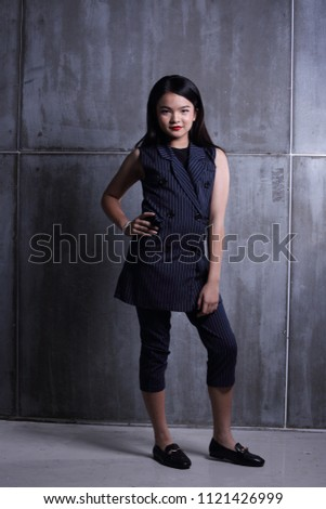 Business Kid Girl in formal suit stand on dark abstract background, studio lighting copy space for text logo, black hair eleven years old full length snap body, Fashion Face Eyes Heart Summer #1121426999