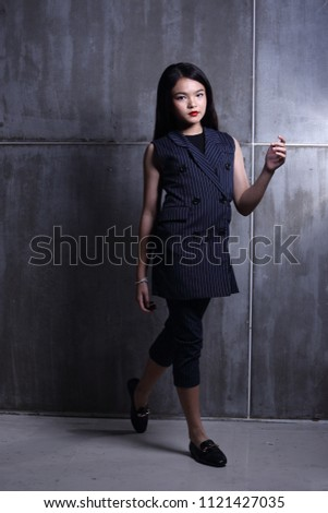 Business Kid Girl in formal suit stand on dark abstract background, studio lighting copy space for text logo, black hair eleven years old full length snap body, walk toward to future #1121427035