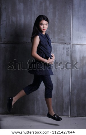 Business Kid Girl in formal suit stand on dark abstract background, studio lighting copy space for text logo, black hair eleven years old full length snap body, jump in the air, motion blur #1121427044