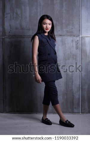Business Kid Girl in formal suit stand on dark abstract background, studio lighting copy space for text logo, black hair eleven years old full length snap body #1190033392