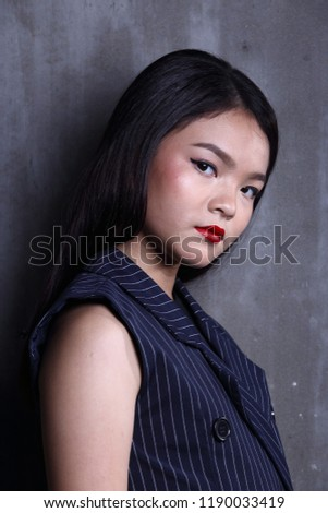 Business Kid Girl in formal suit stand on dark abstract background, studio lighting copy space for text logo, black hair eleven years old portrait half body #1190033419