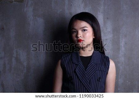 Business Kid Girl in formal suit stand on dark abstract background, studio lighting copy space for text logo, black hair eleven years old portrait half body #1190033425