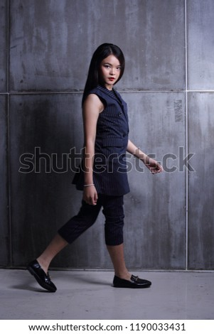 Business Kid Girl in formal suit stand on dark abstract background, studio lighting copy space for text logo, black hair eleven years old full length snap body, walk toward to future #1190033431