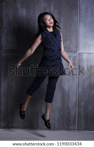 Business Kid Girl in formal suit stand on dark abstract background, studio lighting copy space for text logo, black hair eleven years old full length snap body, jump in the air, motion blur #1190033434