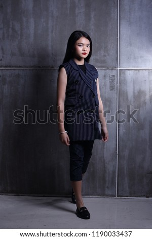 Business Kid Girl in formal suit stand on dark abstract background, studio lighting copy space for text logo, black hair eleven years old full length snap body, walk toward to future #1190033437