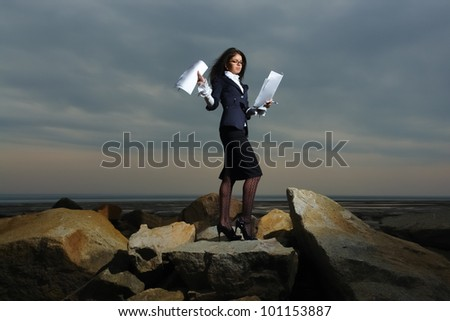 Business ladies standing on rocks by the sea, against the backdrop of a cloudy sky.