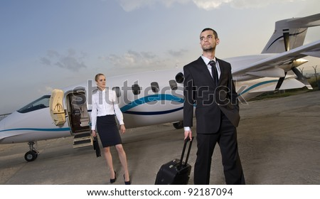 Business lady and businessman coming out of an airplane