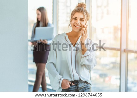Business lady at the office talking to a smartphone. Happy smiling Caucasian business woman busy with phone
